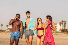 Diverse Friends In Swimwear On Sandy Beach