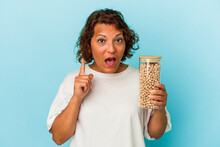 Middle Age Latin Woman Holding Chickpeas Jar Isolated On Blue Background Having Some Great Idea, Concept Of Creativity.