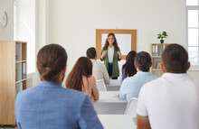 Group Of People Listening To Teacher Sitting At Tables In Modern Classroom, Rear View. Happy Smiling Business Success Course Trainer Or Uni Professor Having Class With Adult Male And Female Students