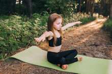 Hardworking, Sweet, Preschool Girl, Child Athlete Sits On A Green Rug In A Lotus Position, Legs Crossed, Performing Sports Exercises, Yoga And Gymnastics, Stretching Her Arms.
