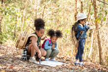 Group Of Diversity Little Girl Friends With Backpack Hiking Together At Forest Mountain In Summer Sunny Day. Three Kids Having Fun Outdoor Activity Sitting And Looking At The Map Exploring The Forest.