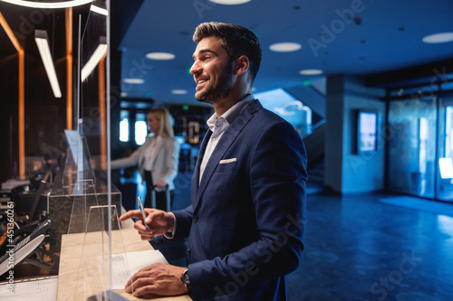 The happy businessman stands at the hotel reception and registers by filling out and signing the form. Business trips, weekdays, lifestyle