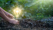 Leinwandbild Motiv Hands of men touching leaf and glowing light bulb on the soil. Symbol. Against nature on green leaf background with icons energy sources for renewable, sustainable development. Ecology concept.