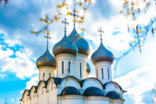 Domes With Eastern Orthodox Crosses On A White Church Against A Blue Sky With Clouds Orthodox Faith. Symbol Of Christianity, Prayer, Repentance For Sins.