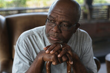 Thoughtful Senior African American Man Sitting And Leaning On The Walking Stick