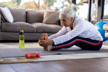 Senior Caucasian Woman In Living Room Sitting On The Floor And Exercising