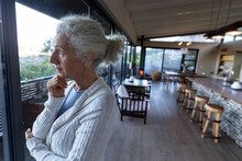 Thoughtful Senior Caucasian Woman In Kitchen Standing And Thinking