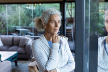 Thoughtful Senior Caucasian Woman In Living Room,looking At The Window