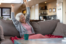Happy Senior Caucasian Woman Sitting On The Couch And Using Tablet In The Modern Living Room