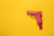 Pink Pistol With Aa Batteries On Pink Background. Concept Art. Minimalism