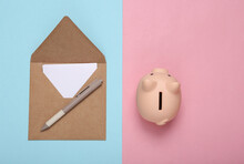 Craft Envelope And Piggy Bank On A Blue-pink Pastel Background. Top View