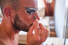 Bearded Man Applying Makeup On Eyes