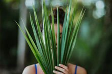 Woman Covering Face With Palm Tree Leaves
