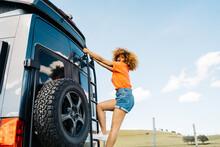 African American Woman Climbing On Van