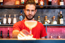 Bartender Serving Cocktail In Glass On Counter In Bar