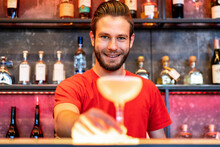 Smiling Bartender Serving Cocktail In Glass On Counter In Bar