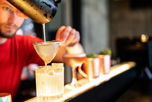 Barman Pouring Cocktail Through Strainer In Glass