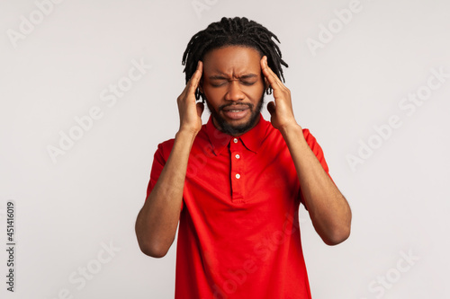 Carta da parati Attractive bearded man with dreadlocks wearing red casual style T-shirt suffering from terrible headache, frowning face, keeping fingers on temples