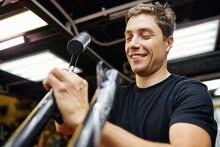 Male Technician Fixing Bike In Garage
