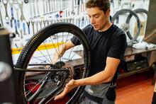 Man Fixing Bicycle Wheel In Garage