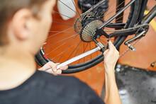 Crop Mechanic Fixing Bike Wheel With Socket Wrench