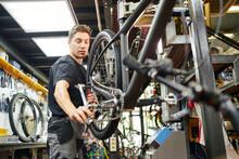 Mechanic Fixing Bike Wheel With Socket Wrench