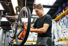 Male Mechanic Wiping Bicycle Frame In Garage