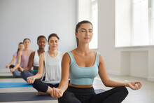 Team Of Beautiful Good Looking Young Women Having Group Meditation Class At Modern Gym Or Yoga Studio, Sitting On Exercise Mats, Doing Lotus Pose, Meditating With Eyes Closed, Increasing Energy Levels