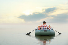 Man Rowing Inflatable Rubber Fishing Boat On River, Back View. Space For Text
