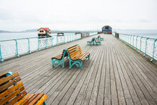 Few Wooden Benches On A Wooden Pier In Front Of New And Old Lifeboat Station. The Mumbles, Wales.