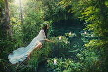 Fabulous Mythical Natural Landscape. Forest Fantasy Woman Sits On Shore Lake, Nymph Throws Wreath In Water. Old Slavic Cult Ceremony Ivan Kupala. Long White Dress. Black Hair