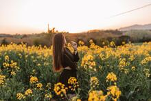 Romantic Brunette Girl In The Field Of Yellow Flowers In Sunbeams