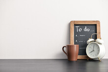 Stylish Workplace With To-do List And Alarm Clock Near Light Wall