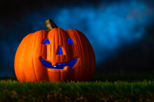 The Symbol Of The Traditional Fall Holiday Halloween Is A Smiling Pumpkin In The Form Of A Head With A Blue Backlight. Green Grass, Dark Night Sky. Advertising, Poster, Banner.