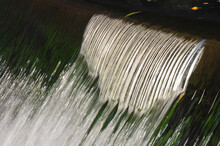 Sparkling Colorful Water Falling Over A Man Made Dam