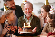 Happy Big Caucasian Family Wearing Party Hats Celebrating Grandfathers Birthday Indoors