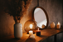 Round Mirror On Wooden Shelf With Two Burning Candles And Small Porcelain Buddha Head