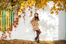 Full Length Portrait Of Stylish Woman Dressed In Beige Coat, Brown Leather Jacket Posing Next To White Wall In Autumn. Blurred Yellow Leaves In The Front, Selective Focus.
