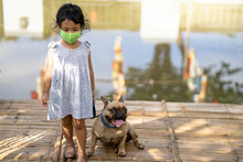 Little Girl Standing At Pond Wearing A Healthy Face Mask With Her Dog.