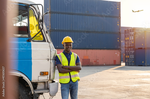 Fototapeta An African truck driver stood resting and smiling happily beside the truck