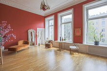 Antique Vintage Interior In 19th Century Style Living Room With Bright Red Walls, Wood Floor And Direct Sunlight Inside The Room.