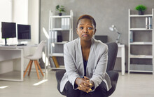 Portrait Of Black Business Woman In Suit Sitting On Office Chair Looking At You With Face Expression That Could Be Interpreted As Both Disappointed Unimpressed And Impressed 'Hmm Not Bad' Expression