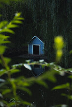 Wooden Bird Feeder Cabin Landscaping Object In Park Pond Reservoir Zone In Dusk Twilight Lighting Time With Unfocused Foliage Vibrant Color Foreground Vertical Photography