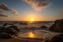 A Beautiful Golden Sunset With Reflections On The Waves Washing Over The Beach And The Sun Setting Behind The Horizon.
