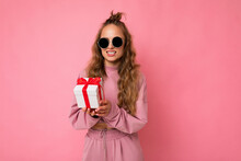 Shot Of Attractive Positive Smiling Young Blonde Woman Isolated Over Colourful Background Wall Wearing Everyday Trendy Outfit Holding Gift Box And Looking At Camera