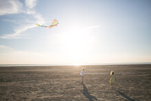A Child Runs With A Kite Along The Shore Of A Salt Lake Of The Sea