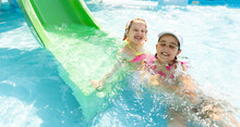 Two Little Girls Fun Jumping Into The Swimming Pool