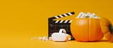 Fototapeta Kawa jest smaczna - Halloween movie night with vr movie, vr headset, popcorn, movie clapper, yellow background