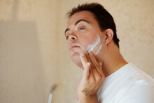 Young Man With Down Syndrome Applying Shaving Cream In The Bathroom