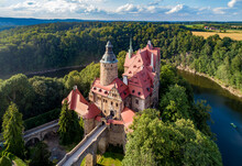 Czocha (Tzschocha) Medieval Castle In Lower Silesia In Poland. Built In 13th Century (the Main Keep) With Many Later Additions. Aerial View In Summer With Kwisa River And Tourist Boat